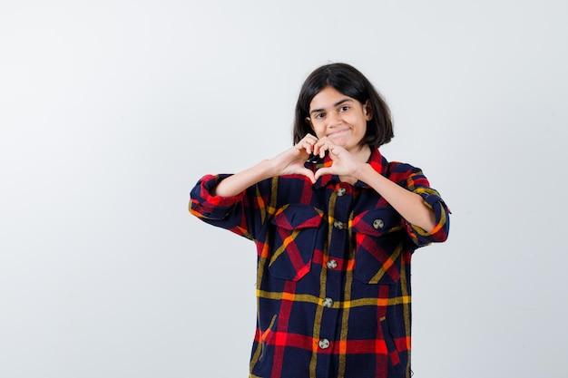 Giovane ragazza che mostra gesto d'amore con le mani in camicia a quadri e sembra felice, vista frontale.