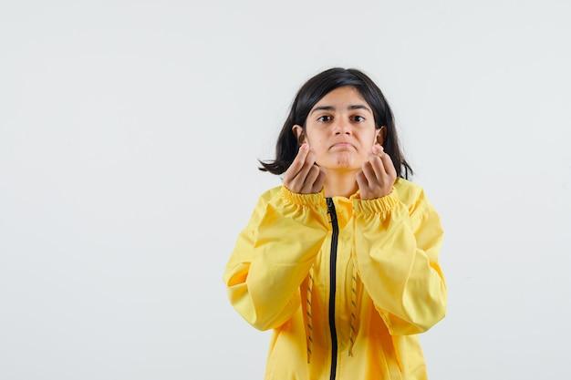 お金のジェスチャーを示し、黄色のボンバージャケットで拳を握りしめ、真剣に見える少女。