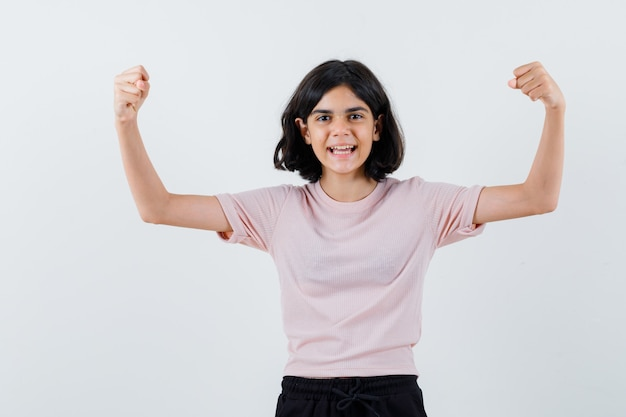 ピンクのtシャツと黒のズボンで筋肉を見せて幸せそうに見える少女