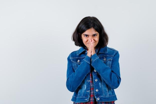 Ragazza che mostra il gesto di namaste in camicia a quadri e giacca di jeans e sembra seria