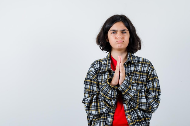 Young girl showing namaste gesture in checked shirt and red t-shirt and looking serious. front view.