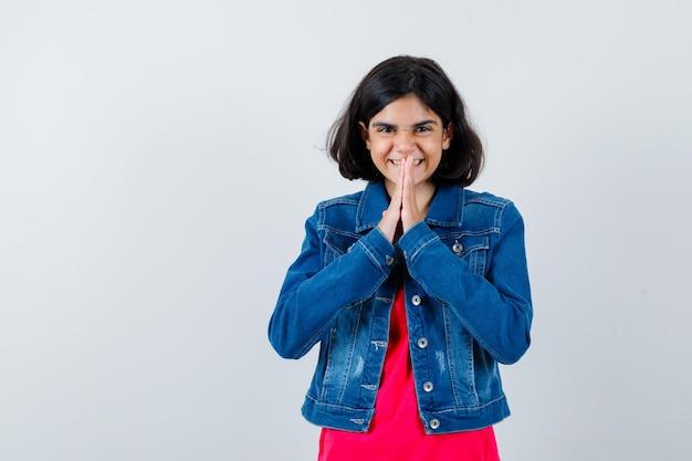 Ragazza che mostra gesto di namaste in maglietta rossa e giacca di jeans e sembra felice. vista frontale.