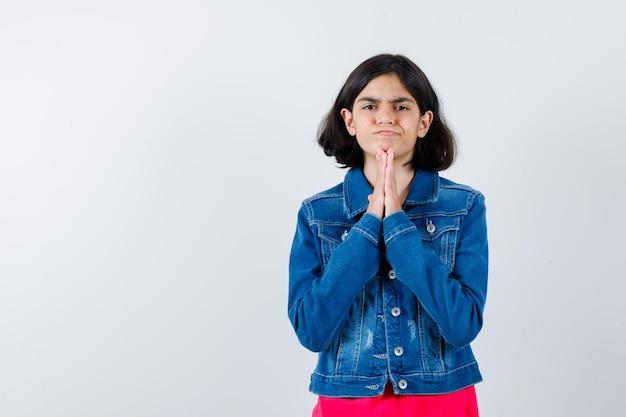 Giovane ragazza che mostra gesto di namaste in maglietta rossa e giacca di jeans e sembra seria, vista frontale.