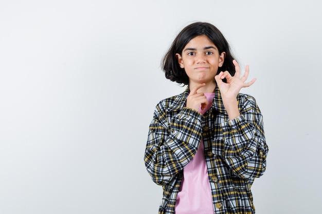 Giovane ragazza che mostra segno ok in camicia a quadri e t-shirt rosa e sembra carina, vista frontale.