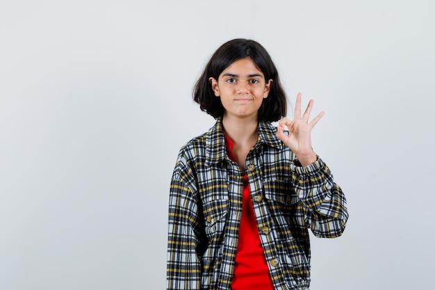 Молодая девушка показывает хорошо подписывается в клетчатой рубашке и красной футболке и выглядит мило. передний план.