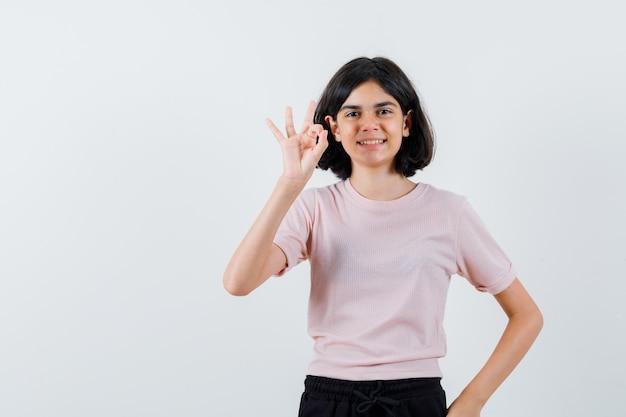 Молодая девушка показывает знак ок в розовой футболке и черных штанах и выглядит счастливой