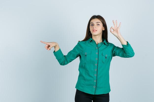 Ragazza che mostra segno giusto, puntando a sinistra con il dito indice in camicetta verde, pantaloni neri e guardando fiducioso, vista frontale.
