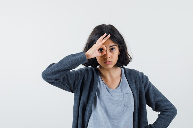 Giovane ragazza che mostra il segno giusto in t-shirt grigio chiaro e felpa con cappuccio con zip grigio scuro e sembra carina.
