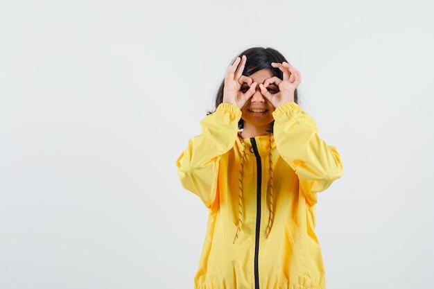 黄色のボンバージャケットと幸せそうに見える目に大丈夫な兆候を示す若い女の子