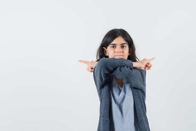 Молодая девушка в светло-серой футболке и темно-серой толстовке на молнии, показывающая противоположные стороны указательными пальцами, выглядит мило.