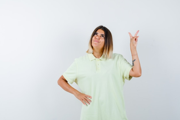 평화 제스처를 보여주는 어린 소녀 티셔츠에 허리에 손을 잡고 잠겨있는, 전면보기를 찾고.