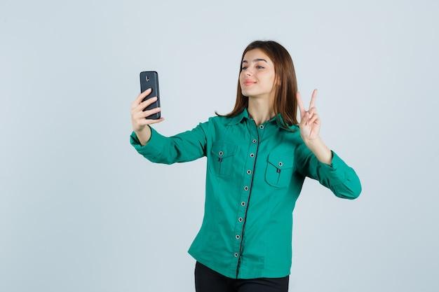 緑のブラウス、黒のズボンでビデオ通話をしながら平和のジェスチャーを示し、かわいく見える、正面図。