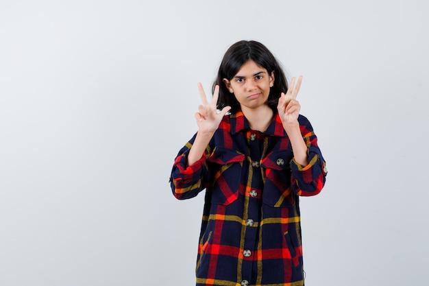 체크 셔츠에 평화 제스처를 보이고 행복해 보이는 어린 소녀. 전면보기.