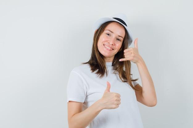 Молодая девушка показывает жест телефона с большим пальцем руки вверх в белой футболке, шляпе и выглядит весело, вид спереди.