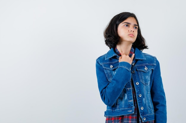 Young girl showing pinky finger while looking away in checked shirt and jean jacket and looking pensive. front view.