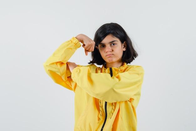 Ragazza che mostra il gesto di potere in giacca bomber gialla e che sembra seria