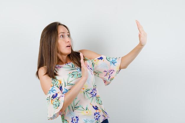 Молодая девушка показывает жест отказа в рубашке, джинсах и выглядит испуганной, вид спереди.