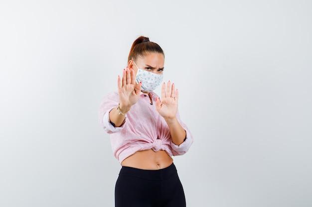 Ragazza che mostra il gesto di restrizione in camicetta rosa, pantaloni neri, maschera e aspetto serio. vista frontale.