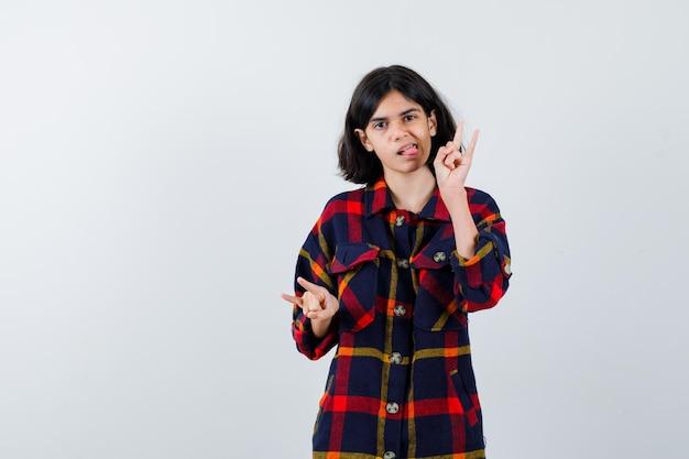 Giovane ragazza che mostra gesti rock'n'roll, tira fuori la lingua in una camicia a quadri e sembra carina. vista frontale.