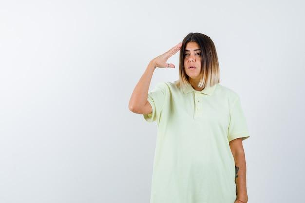 Tシャツで敬礼のジェスチャーを示し、真剣に見える少女、正面図。