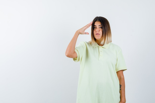 Young girl showing salute gesture in t-shirt and looking serious , front view.