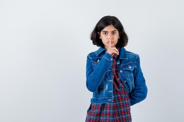 침묵 제스처를 보여주는 어린 소녀, 체크 셔츠와 진 재킷에 허리 뒤에 손을 잡고 귀여운 찾고. 전면보기.