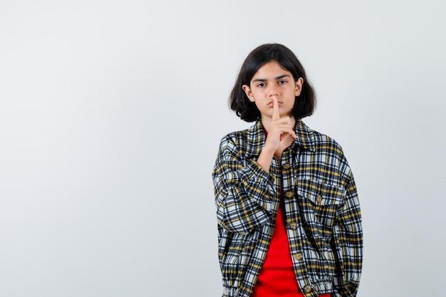 チェックのシャツと赤いtシャツで沈黙のジェスチャーを示し、かわいい、正面図を見て若い女の子。