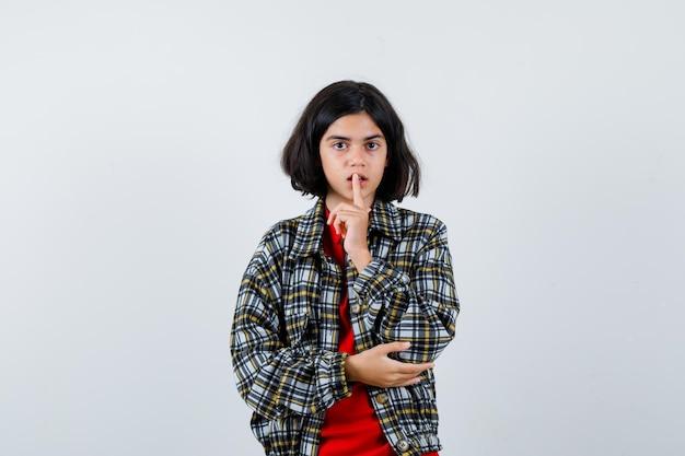 체크 셔츠와 빨간 티셔츠에 침묵 제스처를 보여주는 어린 소녀와 진지한 전면 보기.