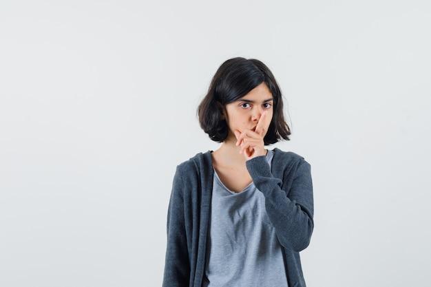 밝은 회색 티셔츠와 어두운 회색 지퍼 앞 까마귀에 침묵 제스처를 보여주는 어린 소녀와 심각한 찾고.