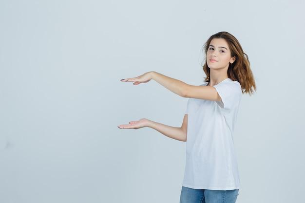 어린 소녀 t- 셔츠, 청바지에 크기 기호를 보여주는 자신감을 찾고. 전면보기.