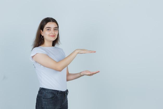 Молодая девушка показывает знак размера в футболке, джинсах и выглядит мило, вид спереди.
