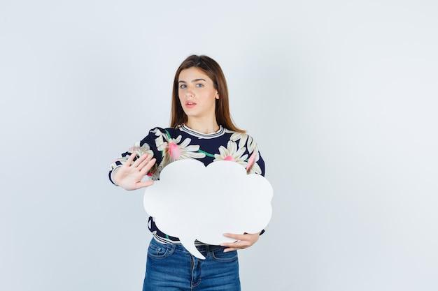 정지 제스처를 보이는 어린 소녀, 꽃무늬 블라우스, 청바지에 종이 포스터를 들고 곤란해 보이는 앞모습.