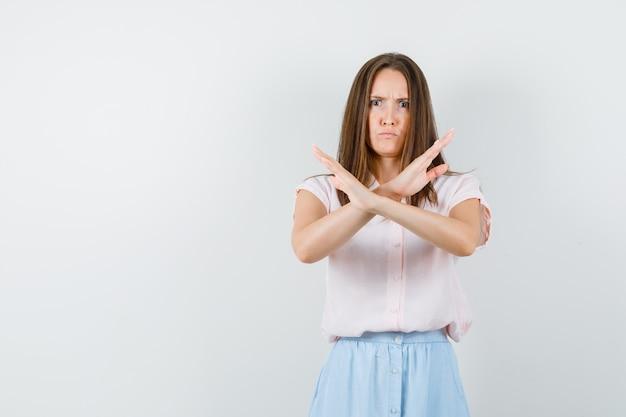 Молодая девушка показывает жест остановки в футболке, юбке и выглядит нервной. передний план.