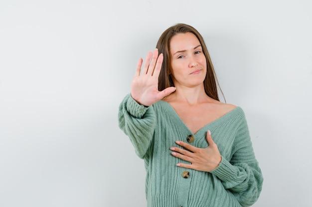 정지 신호를 보여주는 어린 소녀, 니트에 가슴 위에 한 손을 잡고 매력적인, 전면보기를 찾고.