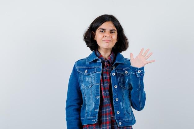 Молодая девушка показывает знак остановки в клетчатой рубашке и джинсовой куртке и выглядит серьезно