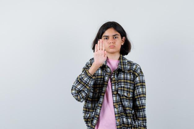 Молодая девушка показывает знак остановки в клетчатой рубашке и розовой футболке и выглядит серьезно. передний план.