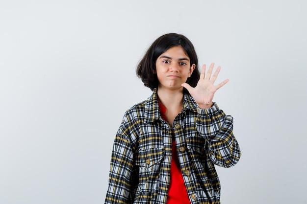 Молодая девушка показывает знак остановки в клетчатой рубашке и красной футболке и выглядит весело, вид спереди.