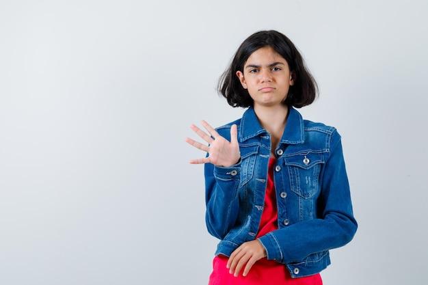 Молодая девушка показывает знак остановки в красной футболке и джинсовой куртке и выглядит серьезно.