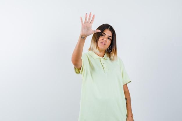 Tシャツで一時停止の標識を示し、自信を持って、正面図を見て若い女の子。