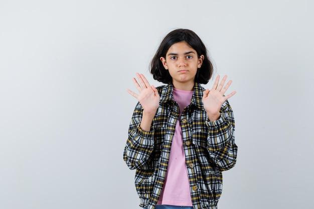 Молодая девушка показывает знаки остановки в клетчатой рубашке и розовой футболке и выглядит серьезной. передний план.