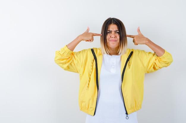 白いtシャツ、黄色のジャケットで自殺ジェスチャーを示し、真剣に見える少女。正面図。