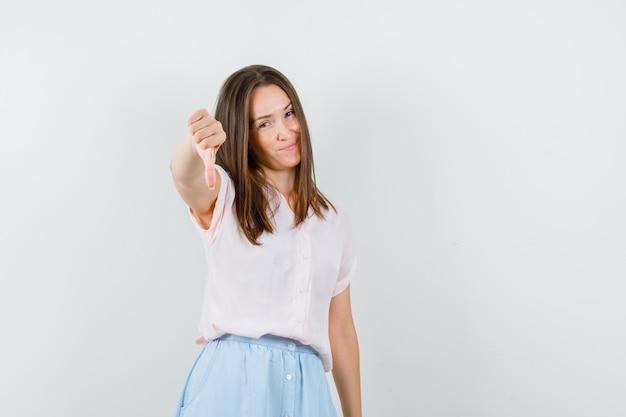 Tシャツ、スカートの正面図で丁寧に親指を下に見せている若い女の子。