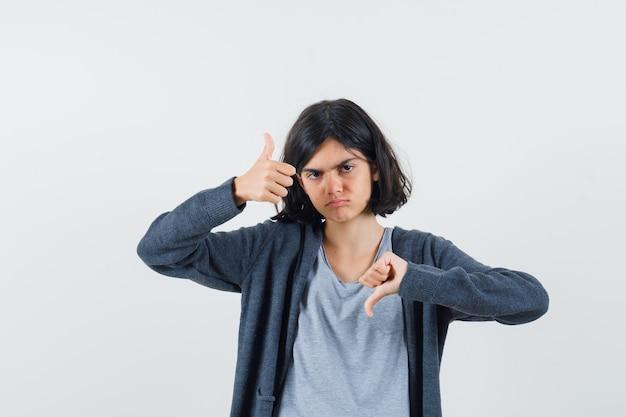 ライトグレーのtシャツとダークグレーのジップフロントフーディーで親指を上下に見せて真剣に見える少女
