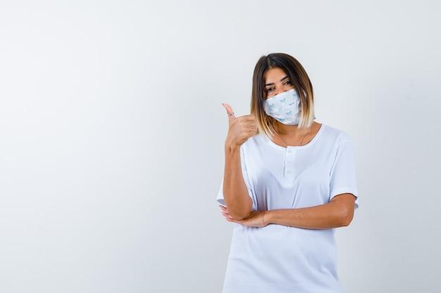 Ragazza che mostra il pollice in su, tenendo la mano sotto il gomito in maglietta bianca e maschera e guardando fiducioso. vista frontale.