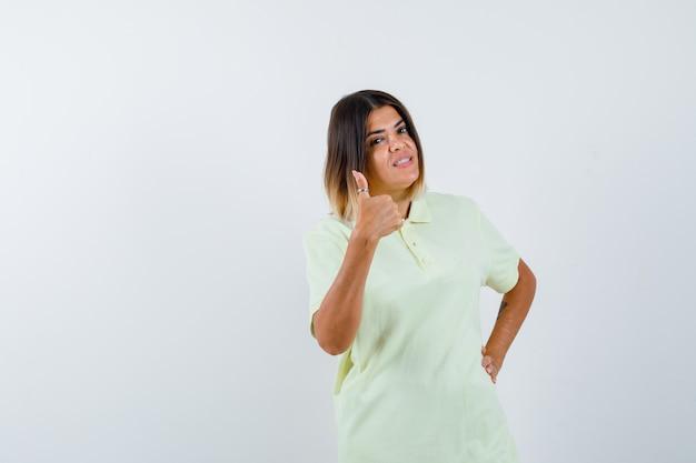 엄지 손가락을 보여주는, t- 셔츠에 허리에 손을 잡고 자신감을 찾고 어린 소녀. 전면보기.