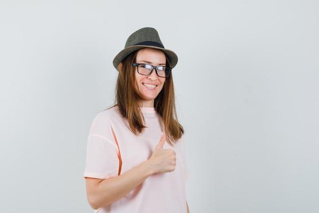 ピンクのtシャツ、帽子、陽気に見える、正面図で親指を表示する若い女の子。