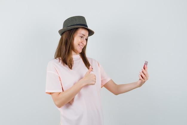 ピンクのtシャツ、帽子、陽気に見える、正面図でビデオチャットに親指を表示する若い女の子。
