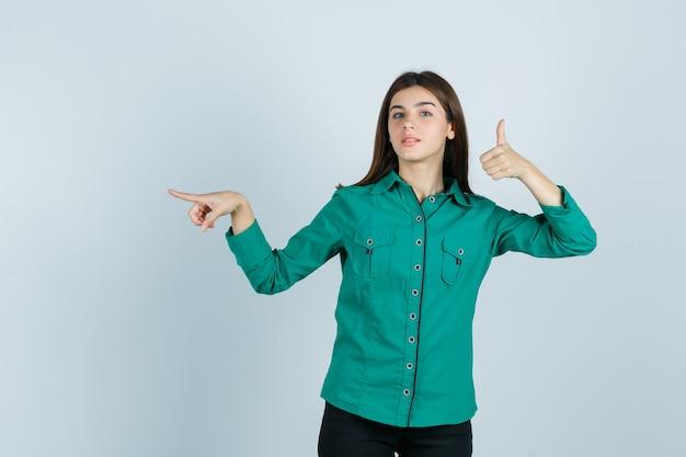 親指を上に向けて、緑のブラウス、黒のズボン、自信を持って、正面図で人差し指で左を指している若い女の子。