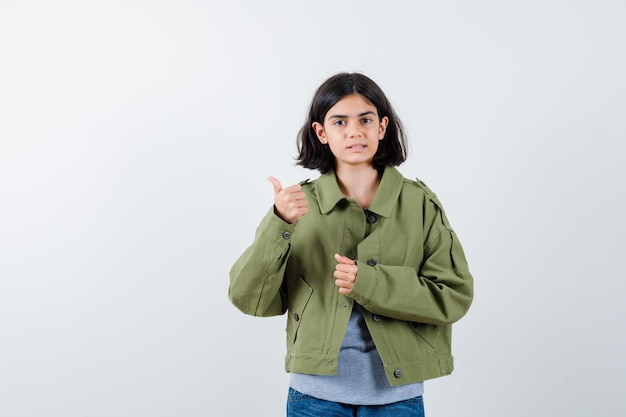 Giovane ragazza che mostra pollice in su mentre stringe il pugno in maglione grigio, giacca color kaki, pantaloni di jeans e sembra carina. vista frontale.