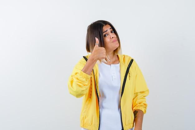 Ragazza che mostra il pollice in su in maglietta bianca, giacca gialla e sembra impressionato, vista frontale.